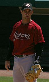 A baseball player standing at first base with his glove